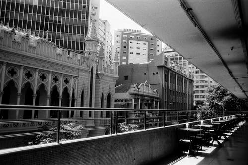 Black and white of narrow balcony terrace with rows of tables against new and old buildings of city