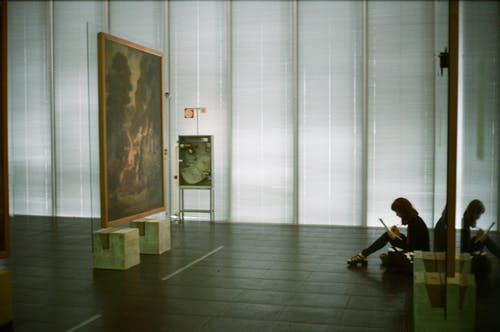 Man in Black Jacket Sitting on Chair Near Painting