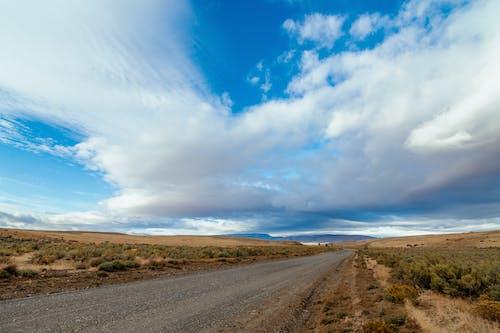 Long straight road running through wild prairie terrain covered dry grass and bushes