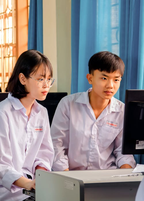 Man and Woman Sitting Down while Looking at the Computer Monitor