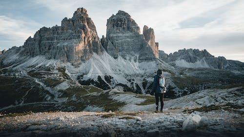 Man in Black Jacket Standing on Rocky Ground Near Rocky Mountain