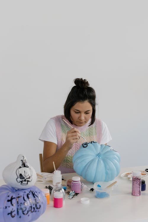 Girl in White T-shirt Holding Blue and White Pumpkin