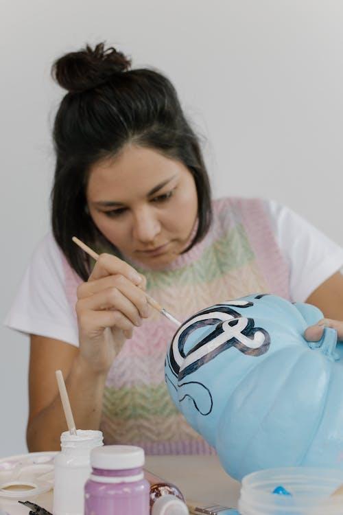 Girl in White Crew Neck T-shirt Holding White Pen