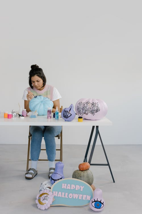 Girl in Pink Shirt and Blue Denim Jeans Sitting on White Wooden Table