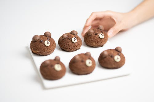 Person Holding Brown Cookies on White Table