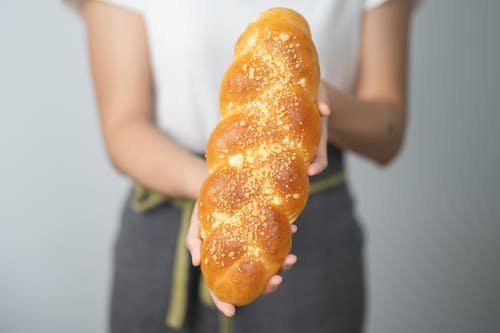 Person Holding Bread With Orange Filling