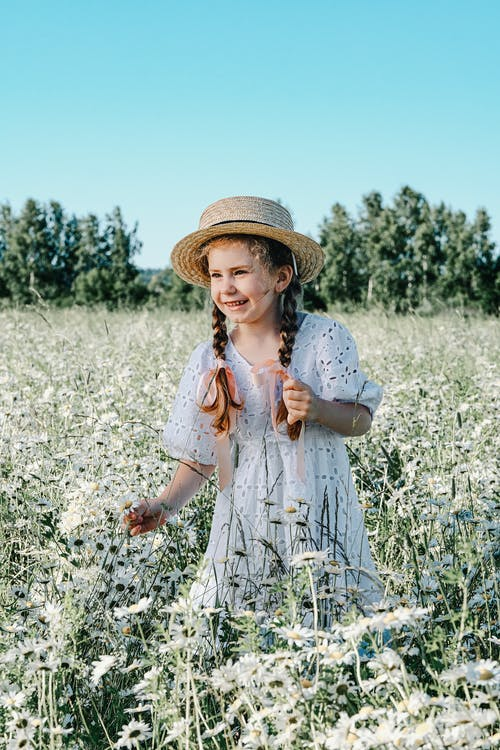 Happy cute girl wearing stylish white sundress and hat strolling on lush blossoming field in summer nature on fair weather