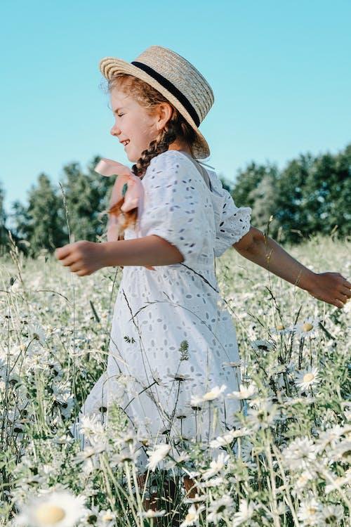 Cheerful girl walking on chamomile field