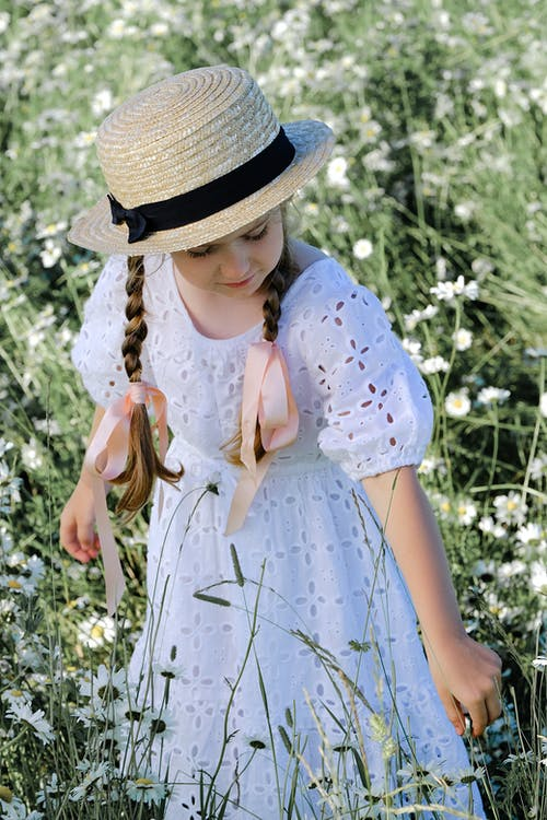 Girl in White and Blue Floral Dress Wearing Brown Straw Hat
