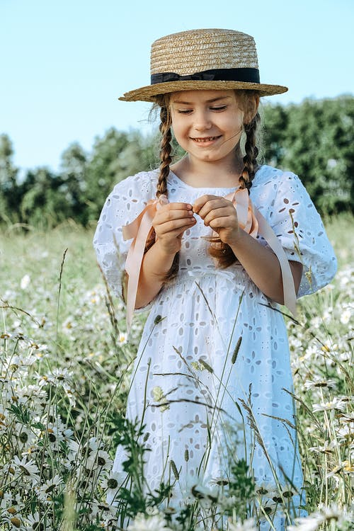 Cheerful stylish girl in white sundress and straw hat standing on chamomile lawn in lush nature on sunny day