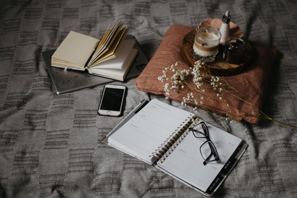 White Notebook Beside Silver Iphone 6 on Brown Wooden Table