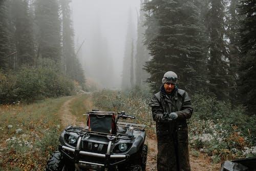 Male traveler in raincoat on path near ATV between woods