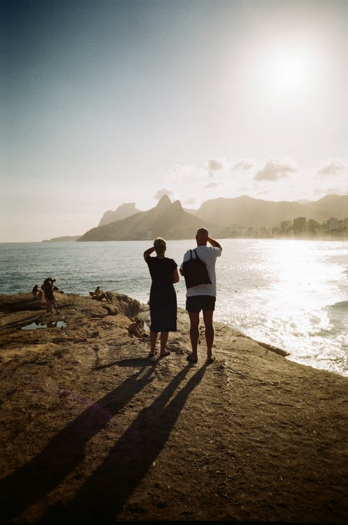 Man and Woman Standing on Brown Rock Near Body of Water