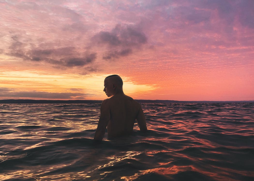 Man in Body of Water during Sunset