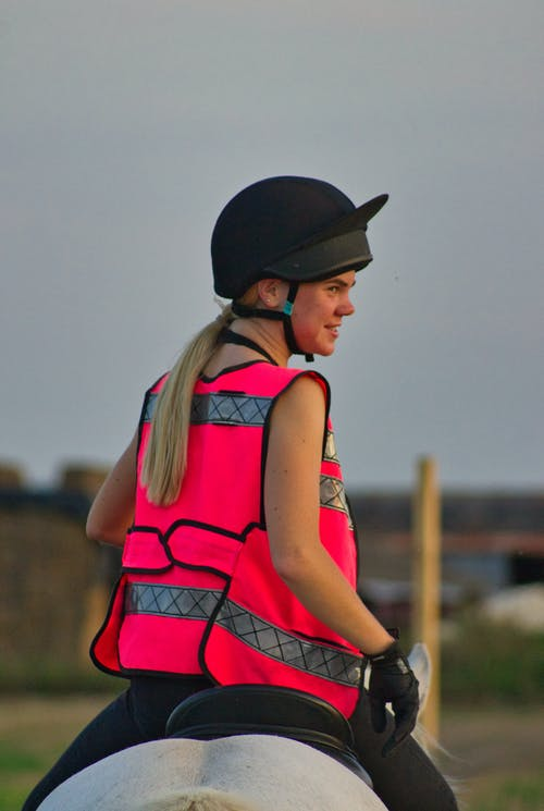 Back view of positive young female equestrian in bright vest and helmet sitting on gray horse and looking away on sunny day in countryside