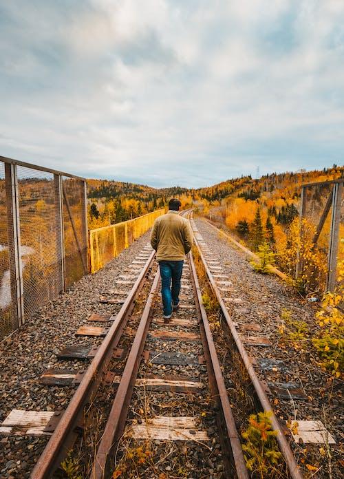 Man in Green Jacket Walking on Train Rail