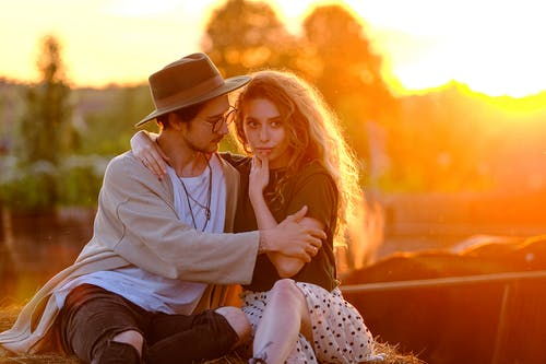 Loving couple embracing on roof in countryside at sunset