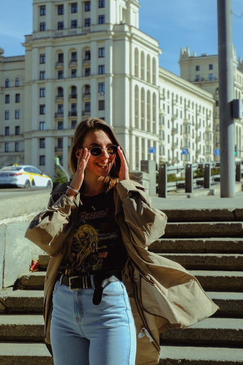 Trendy woman in sunglasses near city stairs