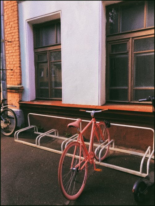 Old fashioned bicycle fixed to metal structure for parking bicycles near facade of building with windows on street in daytime