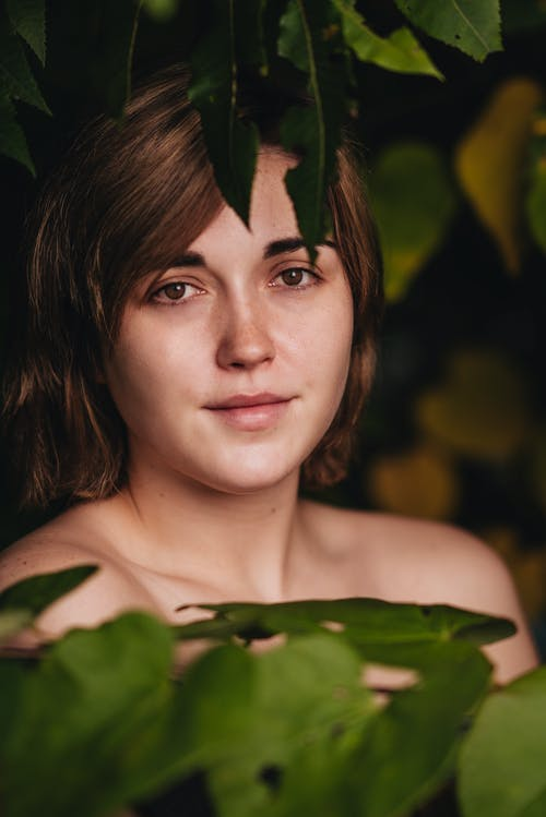 Attractive young positive female with bare shoulders amidst lush tree branches with green leaves and looking at camera contentedly