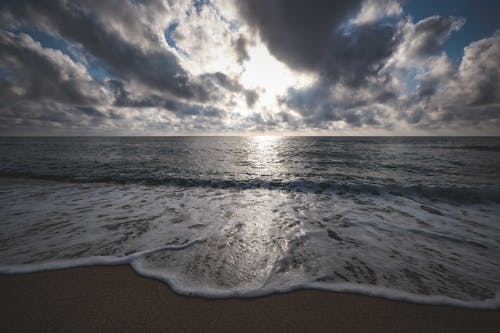 Picturesque view of ocean foamy waves on sandy beach under clouds at sundown
