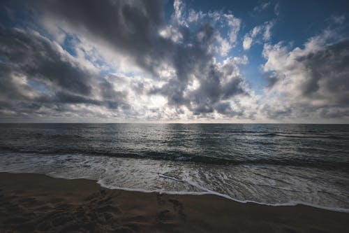 Waving sea under cloudy sky at sunset