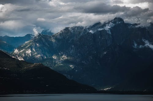 Picturesque view of rough ridge of mountain near hill slope and lake under cloudy sky