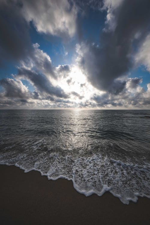 Picturesque view of foamy waves of ocean washing sandy shore under cloudy sky at sundown