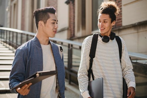 Multiracial students communicating and walking downstairs