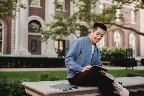 Asian male using tablet while resting on bench in park near building