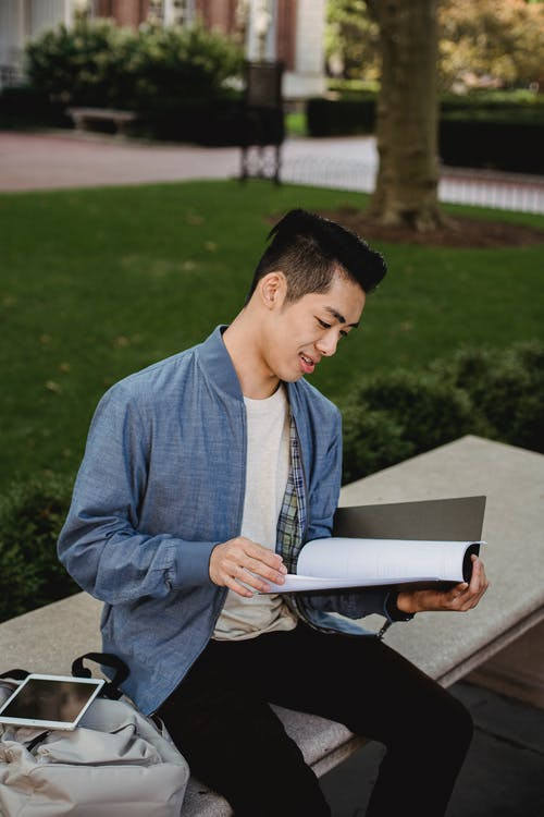 Pensive Asian student reading documents on street