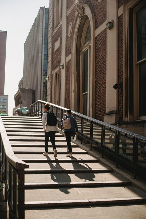 Back view of anonymous friends in casual clothes with backpacks walking upstairs along building in city in sunny day