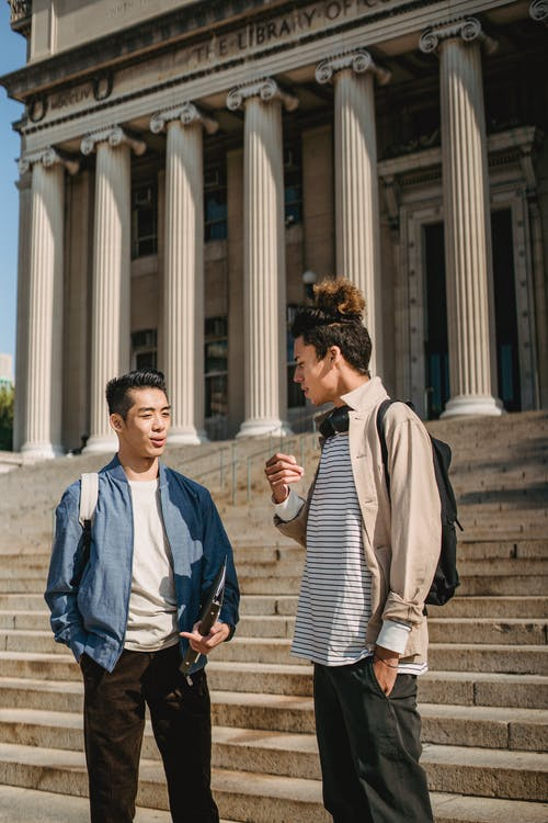 Young multiracial male students talking to each other standing together on stairs of aged university building with columns