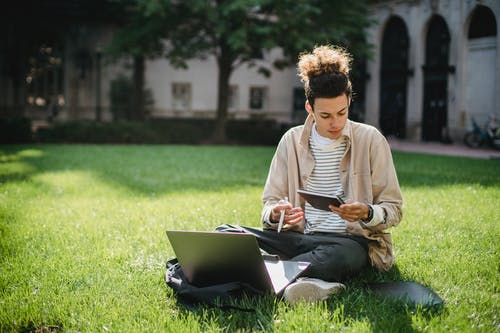 Concentrated student sitting on grass with notepad and laptop while working on homework assignment in park
