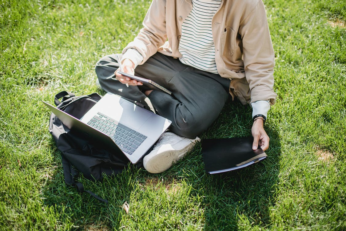 Young student with laptop and notebooks studying in park