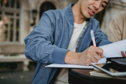 Crop Asian man writing in document while preparing for lesson with friend in park