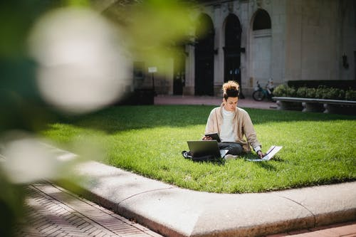 Focused ethnic man studying on lawn in university campus