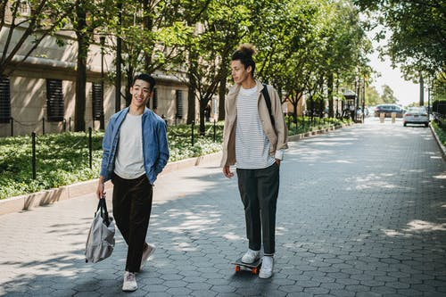 Full body positive young multiracial male friends wearing casual outfits chatting while riding skateboard and strolling together along sunny paved walkway in modern city