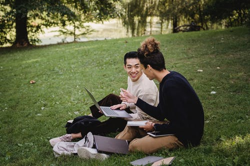 Side view full length smiling ethnic male students in casual outfits resting on grassy lawn with laptop and textbooks while preparing for exams together in green park