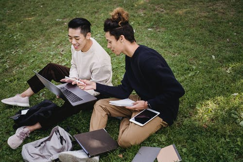 High angle full length ethnic male students in casual clothes browsing laptop and discussing college project while sitting together on grassy meadow in park