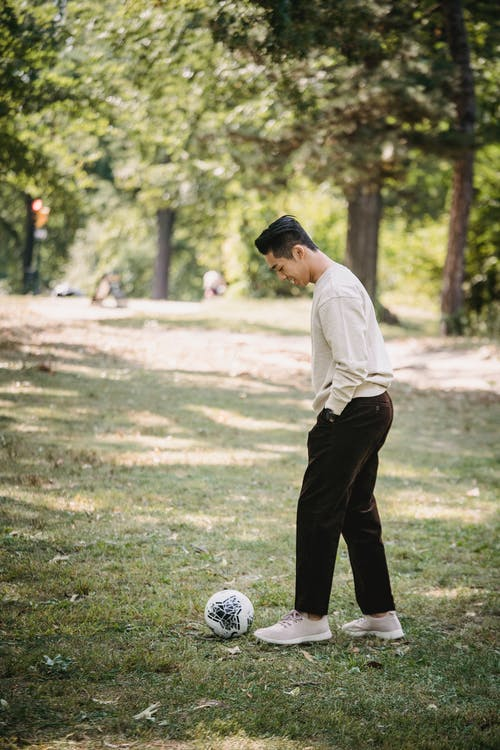 Cheerful ethnic man playing with soccer ball in park