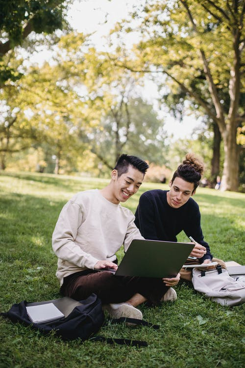 Full length content ethnic male students in casual outfits browsing laptop while sitting on meadow with copybooks and preparing for exam in green park