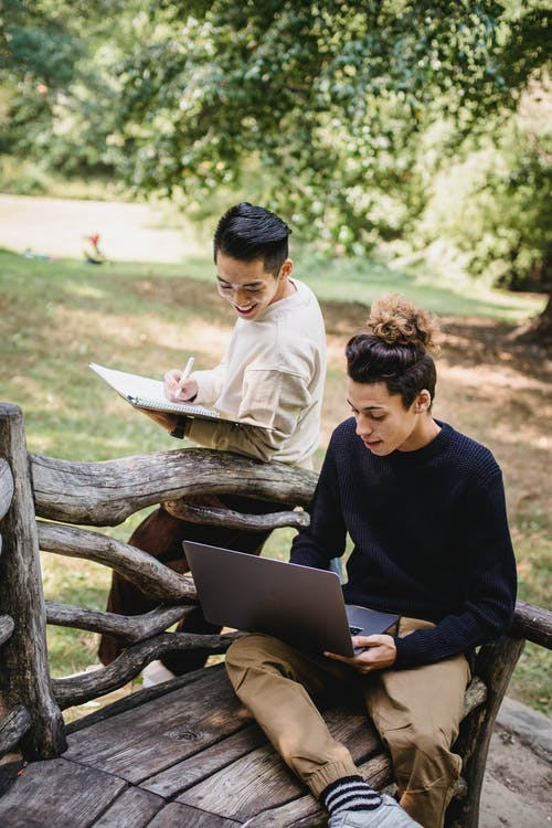 Happy young ethnic male students in casual outfits browsing modern laptop and taking notes in notebook while studying together in sunny park