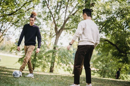 Positive ethnic male friends playing football in park