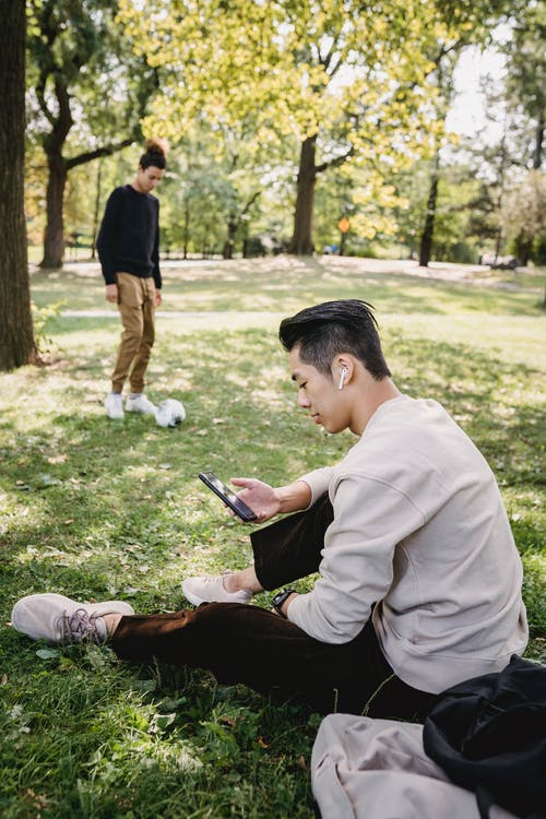Side view full body young ethnic male in casual clothes and earbuds resting on grass in park and using modern smartphone near friends playing with football ball