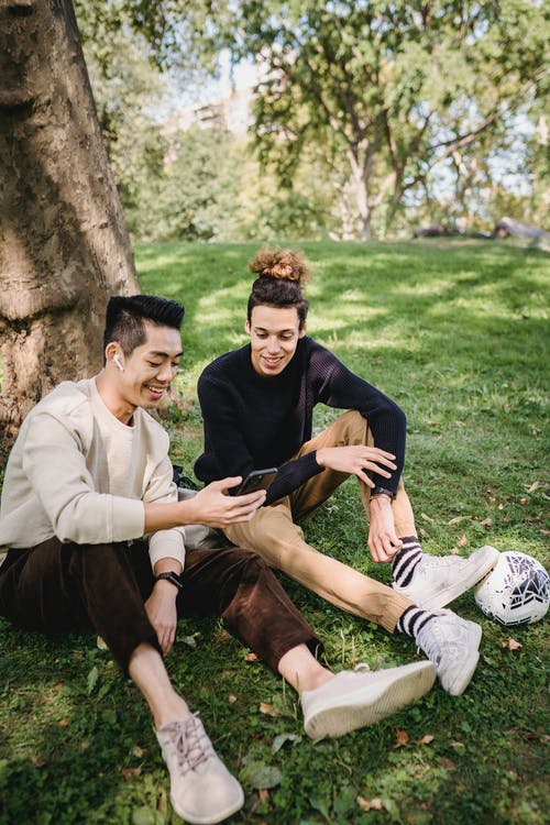 Smiling young ethnic males in casual clothes watching funny video on modern mobile phone while resting together on grass meadow in park