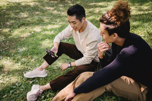 From above content young ethnic male friends wearing casual outfits surfing internet on modern mobile phone and sitting on grass in sunny park