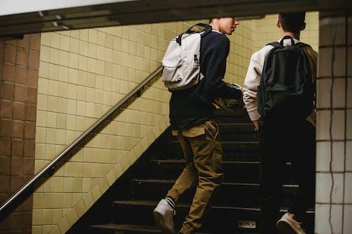Crop male friends going upstairs in underground passage