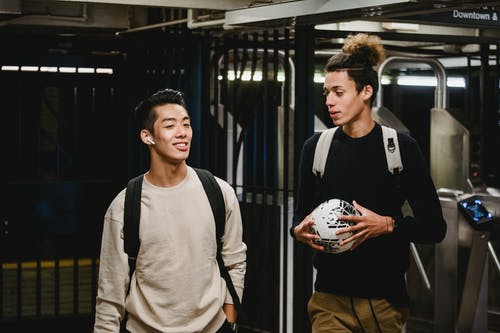 Cheerful ethnic male friends in casual sweaters with backpacks and soccer ball walking in modern metro station and having conversation