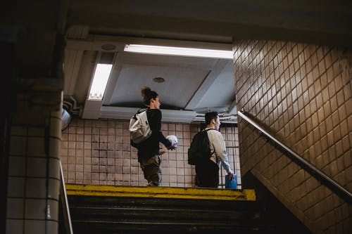 Young men walking on metro staircase